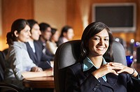 Portrait of a businesswoman sitting with her colleagues in a conference room and smiling