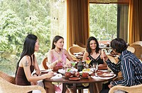 Three young women and a young man dining in a restaurant (thumbnail)