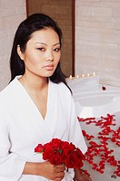 Portrait of a young woman holding a bunch of roses near a bathtub