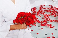 Mid section view of a woman holding a bunch of roses near a bathtub