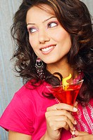 Close-up of a young woman holding a martini glass and smiling