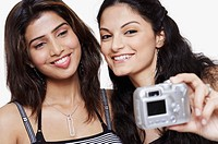 Close-up of two young women taking a photograph of themselves