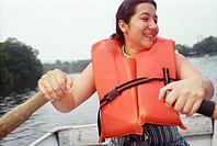 Latino woman rowing boat.