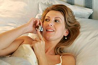 Elevated close_up view on woman laying in bed and talking on cellphone