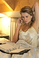 Middle_aged blonde woman sitting in bed, looking at agenda and listening to cellphone