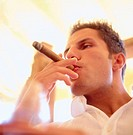 Close_up of a young man smoking cigar