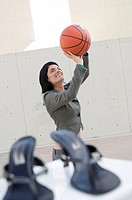 Businesswoman playing basketball