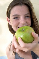 Portrait of a teenage girl holding an apple