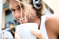 Close-up of a young man wearing headphones and holding a cup