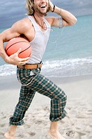 Side profile of a young man playing with a basketball on the beach