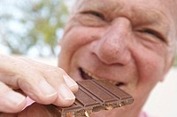 Portrait of a senior man eating a chocolate bar