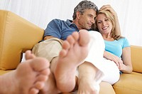 Mid adult couple reclining on a couch