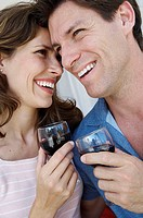Close-up of a young couple smiling and holding wineglasses