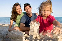 Parents making a sand castle with their son and daughter