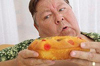 Close-up of a mature man holding a burger and looking sideways