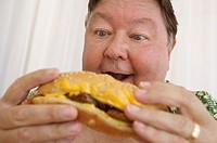 Close-up of a mature man with his mouth open and looking at a burger