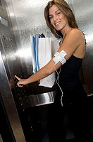 Portrait of a young woman standing in an elevator holding shopping bags