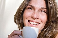 Close-up of a young woman holding a cup of tea and smiling
