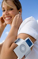 Portrait of a young woman listening to an MP3 player