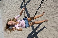 High angle view of a young woman sitting on a swing and holding a mobile phone