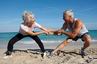 Senior couple standing and holding hands on the beach
