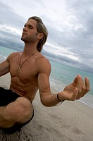 Close-up of a young man meditating on the beach