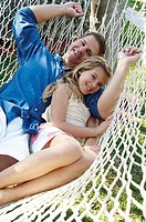 High angle view of a mid adult man and his daughter lying in a hammock and smiling