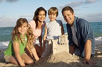 Close-up of a mid adult couple and their two children behind a sandcastle