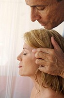 Side profile of a mid adult woman getting a massage by a mid adult man