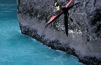 Kayakker launching from the granite shore into the river Futaleuvu, Patagonia, Chile