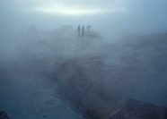 Hot springs in the desert of Uyuni, southern Bolivia, on a misty morning  A couple takes a photo on the edge off a cliff
