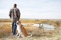 Man standing with dog in countryside