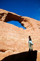 Female hiker viewing Skyline Arch from a large boulder below, Arches National Park, Utah, USA