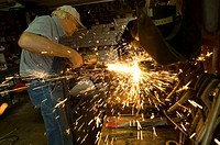 Sparks fly as a man uses a grinder at his Nebraska farm