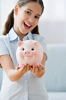 Smiling girl holding a piggy bank