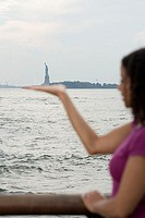 Woman pretending to hold statue of liberty