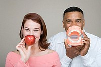 Dentist and woman holding an apple and false teeth (thumbnail)