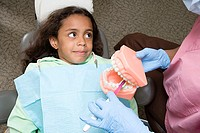 Dental nurse showing girl how to clean teeth
