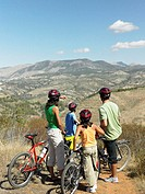 Family with bicycles looking at view