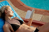 Picture of a blonde woman in a black bikini lying on a sunlounger by a pool and reading a book
