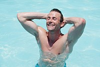 Horizontal shot of a good-looking man with a muscular torso in a swimming pool in India