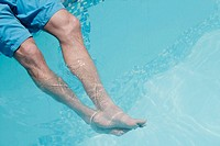 Horizontal shot of a man's legs in a swimming pool in India