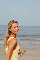 Beautiful blonde woman wearing headphones and smiling on a beach in India