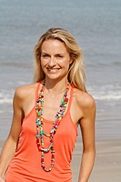 Portrait of a beautiful blonde woman wearing an orange vest and smiling on a beach in India