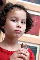 Girl eating a chocolate bar  She is six years old