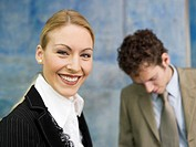 Business woman smiling, man standing behind, close up