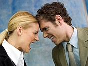 Businessman and businesswoman quarrelling, side view, close up