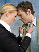 Businesswoman grabbing man by tie, shouting, side view, close-up