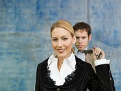 Businesswoman pulling businessman's tie, smiling (thumbnail)