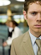 Young businessman, portrait, women in background (thumbnail)